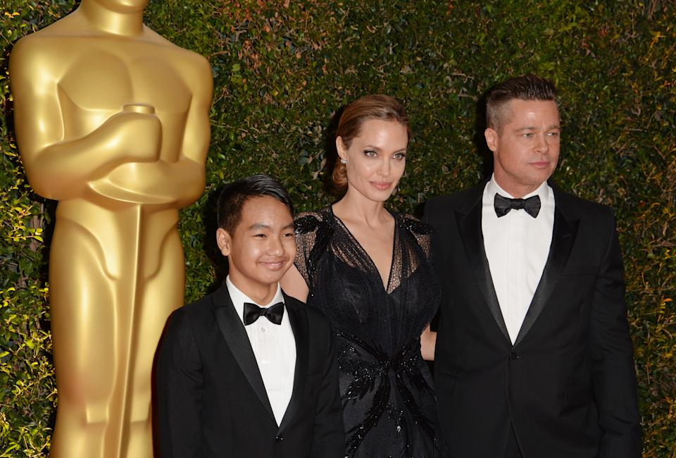 Actress Angelina Jolie, Maddox Jolie-Pitt (L) and actor Brad Pitt arrive for the 2013 Governors Awards, presented by the American Academy of Motion Picture Arts and Sciences (AMPAS), at the Grand Ballroom of the Hollywood and Highland Center in Hollywood, California, November 16, 2013.  AFP PHOTO / Robyn Beck        (Photo credit should read ROBYN BECK/AFP via Getty Images)