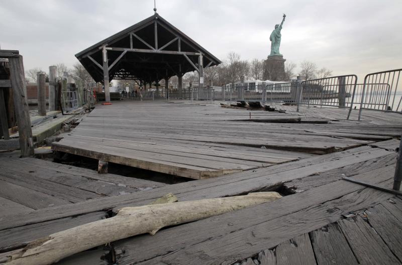 FILE- In this Nov. 30, 2012 file photo, boards of the passenger dock of Liberty Island in New York are askew, damaged from Superstorm Sandy. After hundreds of National Park Service workers from as far away as California and Alaska spent weeks cleaning and making repairs, the island will reopen to the public on Independence Day, July 4, 2013. (AP Photo/Richard Drew, File)