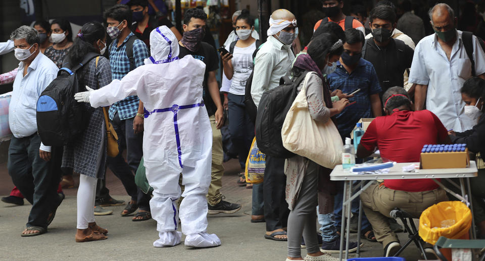 A health worker in protective suit directs arriving passengers towards the COVID-19 testing counter outside a train station in Bengaluru, India.