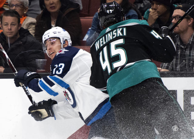 Winnipeg Jets left wing Brandon Tanev, left, gets hit by Anaheim Ducks defenseman Andy Welinski during the first period of an NHL hockey game in Anaheim, Calif., Wednesday, March 20, 2019. (AP Photo/Kyusung Gong)