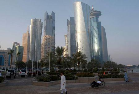 A man walks on the corniche in Doha