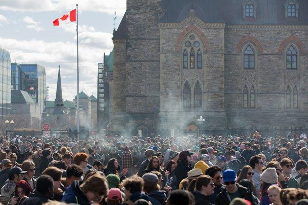 Smoke lingers over Parliament Hill in Ottawa, Ontario, as people smoke marijuana during the annual 4/20 rally on April 20, 2018.