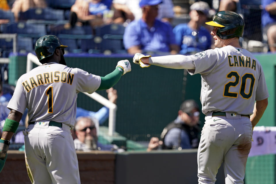 Oakland Athletics' Josh Harrison (1) and Mark Canha (20) celebrate after scoring on a single by Chad Pinder during the third inning of a baseball game against the Kansas City Royals Thursday, Sept. 16, 2021, in Kansas City, Mo. (AP Photo/Charlie Riedel)