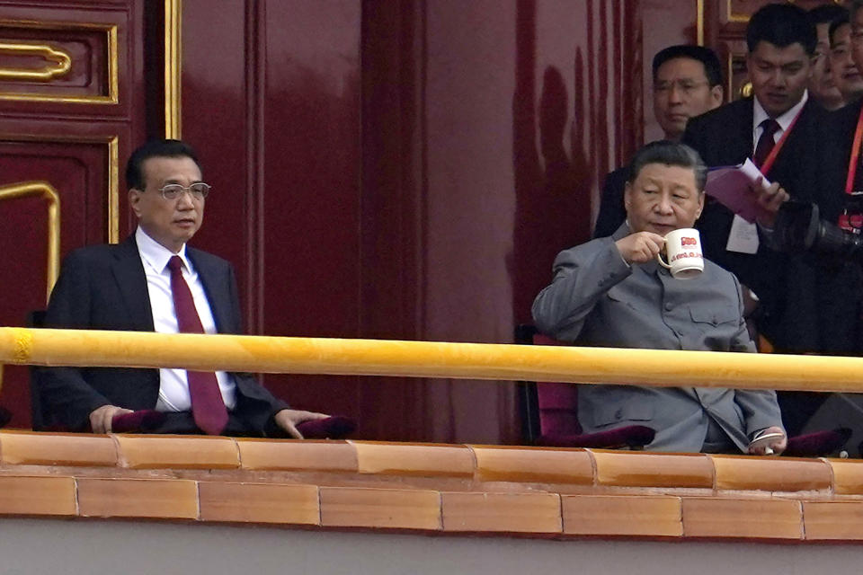 Chinese President Xi Jinping, right, drinks from an anniversary mug as he looks over towards Chinese Premier Li Keqiang during a ceremony to mark the 100th anniversary of the founding of the ruling Chinese Communist Party at Tiananmen Gate in Beijing Thursday, July 1, 2021. (AP Photo/Ng Han Guan)