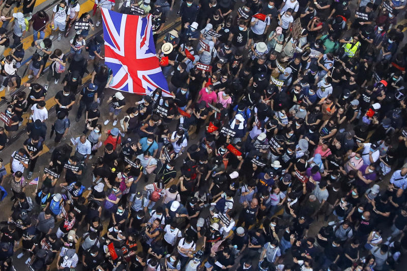Protesters carry a British flag gather at a shopping district during a rally in Hong Kong, Sunday, Sept. 15, 2019. Thousands of Hong Kong people chanted slogans and marched Sunday at a downtown shopping district in defiance of a police ban, with shops shuttered amid fears of renewed violence in the months-long protests for democratic reforms in the semi-autonomous Chinese territory. (AP Photo/Kin Cheung)