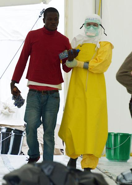 A health worker, wearing Personal Protective Equipment (PPE), arrives with a potentially contaminated patient on September 7, 2014 at Elwa hospital in Monrovia (AFP Photo/Dominique Faget)