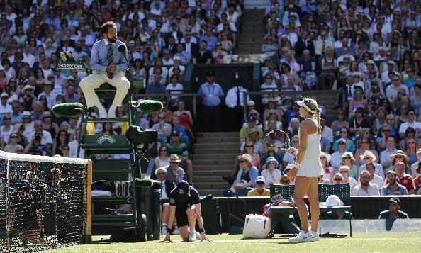 Eugenie Bouchard of Canada talks to the umpire during the women's singles semifinal match against Simona Halep of Romania at the All England Lawn Tennis Championships in Wimbledon, London, Thursday, July 3, 2014. (AP Photo/Ben Curtis)