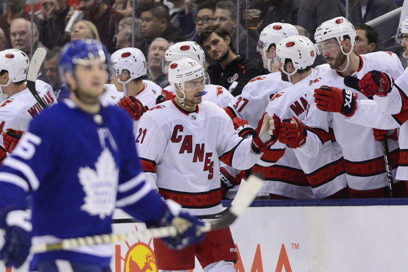 Carolina Hurricanes right wing Nino Niederreiter (21) celebrates after scoring against Toronto Maple Leafs goaltender Frederik Andersen with teammates at his bench during second-period NHL hockey game action in Toronto, Saturday, Feb. 22, 2020. (Frank Gunn/The Canadian Press via AP)
