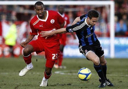 Tyrone Barnett (L) of Crawley Town and Matthew Upson of Stoke City fight for the ball during their FA Cup soccer match at Broadfield Stadium in Crawley, southern England, February 19, 2012. REUTERS/Andrew Winning