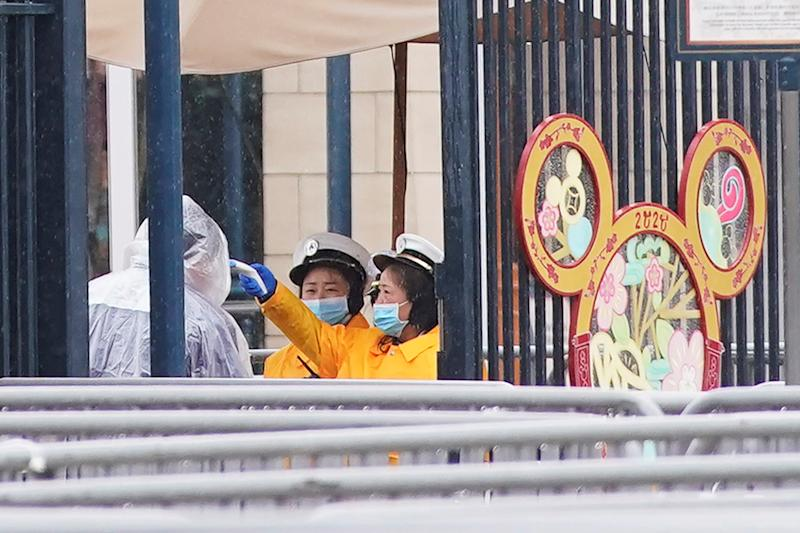 Members of staff check the temperature of a staff member at an entrance of the Shanghai Disney Resort, that is closed today during the Chinese Lunar New Year holiday following the outbreak of a new coronavirus, in Shanghai, China January 25, 2020. REUTERS/Aly Song