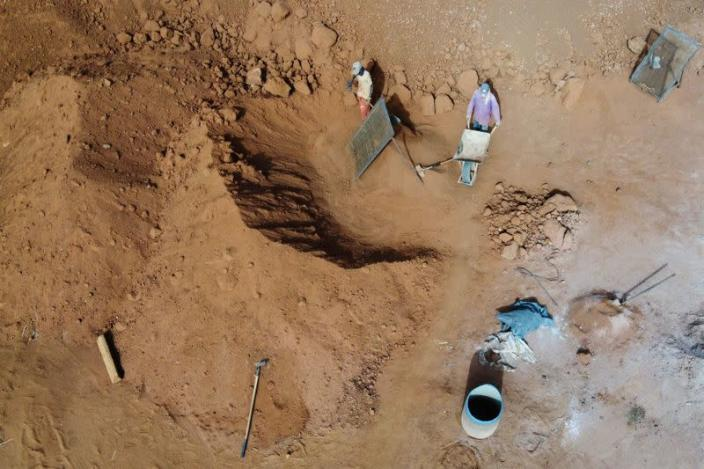 Workers separate raw soil and rocks at the Elementerre factory in Mbour