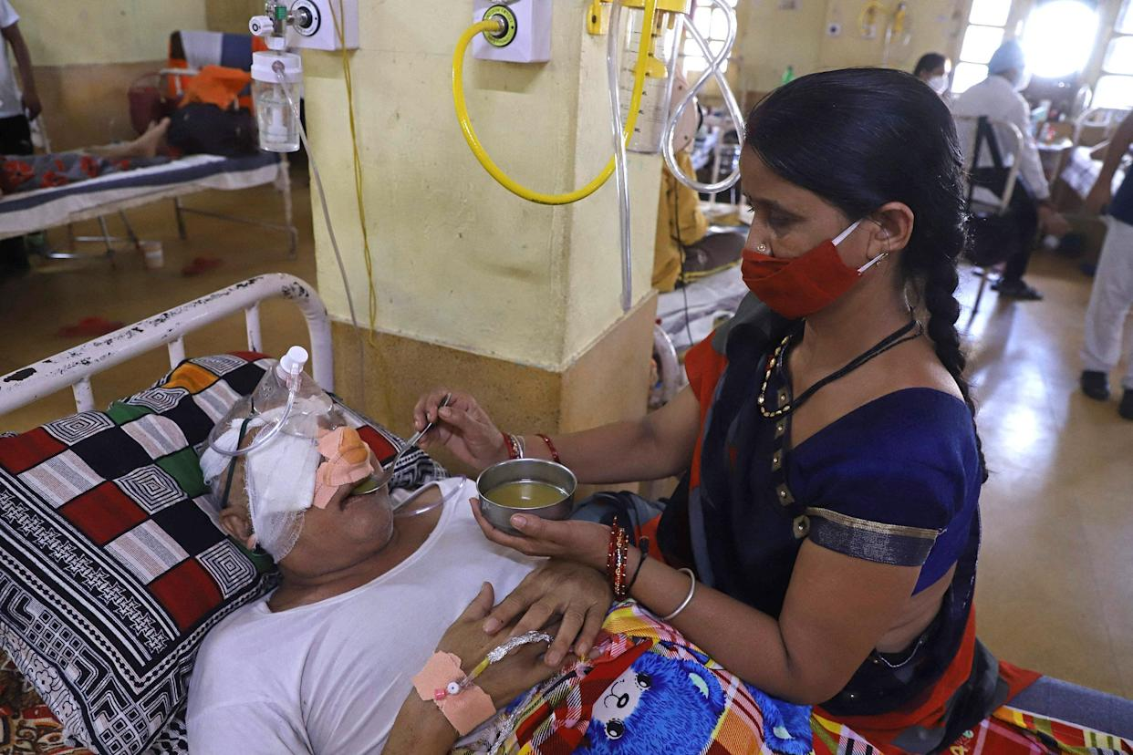 Image: An attendant sits next to a patient who recovered from the Covid-19 coronavirus and is now infected with the deadly fungal infection in Jabalpur on Friday. (Uma Shankar Mishra / AFP - Getty Images)