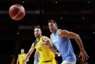 Australia's Nic Kay (15) and Argentina's Luis Scola (4) eye a loose ball during a men's basketball quarterfinal round game at the 2020 Summer Olympics, Tuesday, Aug. 3, 2021, in Saitama, Japan. (AP Photo/Charlie Neibergall)