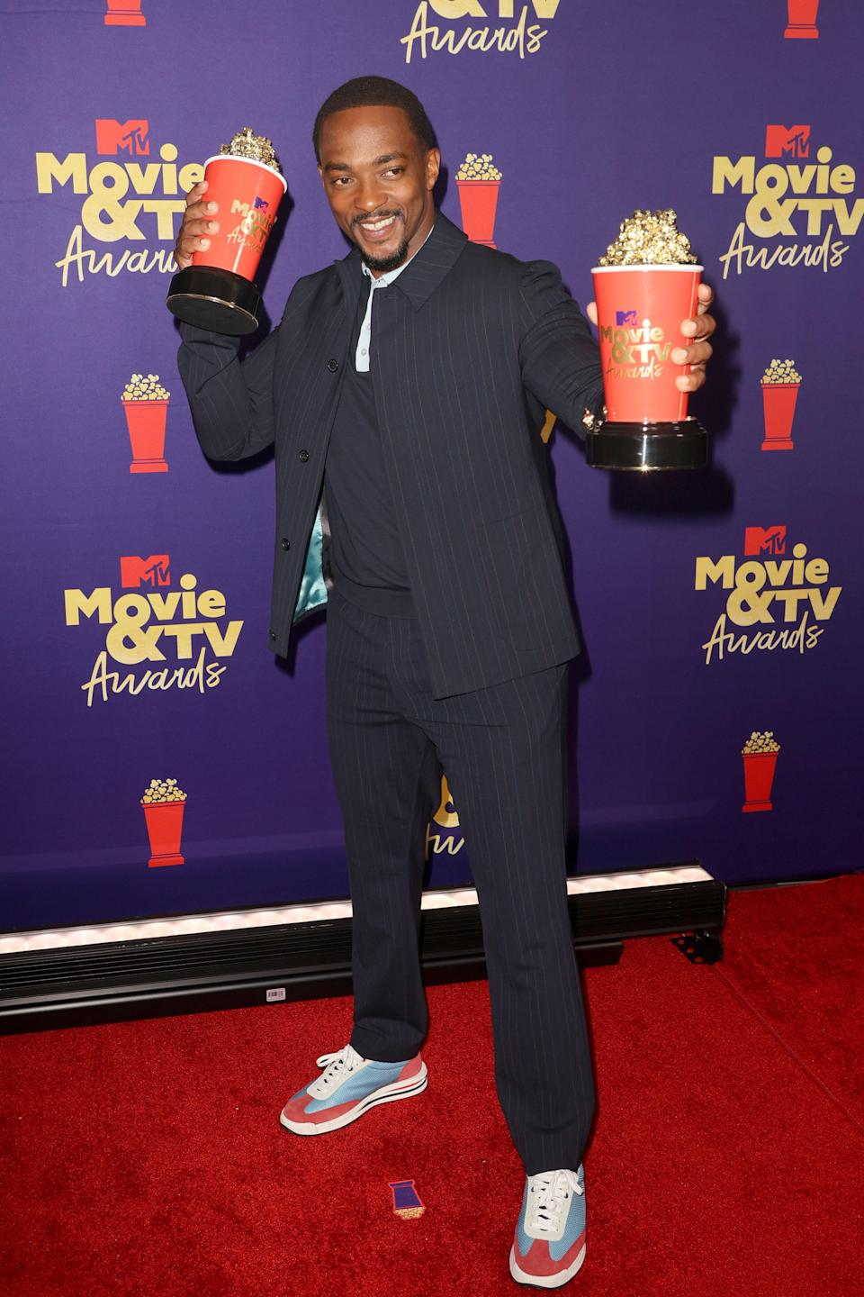 """Marvel actor Anthony Mackie wore a casual striped suit that drew all the attention to his red and blue sneakers. The color scheme almost felt like an ode to his Captain America costume in Disney+ series <a href=""""https://www.teenvogue.com/story/what-falcon-and-the-winter-soldier-teaches-us-about-fandom-misogynoir?mbid=synd_yahoo_rss"""" rel=""""nofollow noopener"""" target=""""_blank"""" data-ylk=""""slk:Falcon and the Winter Soldier."""" class=""""link rapid-noclick-resp""""><em>Falcon and the Winter Soldier.</em></a>"""