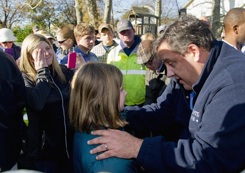New Jersey Gov. Chris Christie gives little 9-year-old Ginjer Doherty a pep talk outside the Port Monmouth fire station in Port Monmouth, N.J., where he visited residents and first responders Monday, Nov. 5, 2012 a week after Hurricane Sandy devasted New Jersey.  At left, wiping her eye, is Ginjer's mom, Gail. (AP Photo/The Philadelphia Inquirer, Clem Murray, Pool)