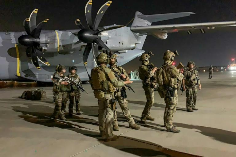 French special forces soldiers stand guard near a military plane at the airport in Kabul after arriving to evacuate French and Afghan nationals following the Taliban's stunning military takeover