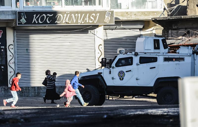 Residents walk past an armoured special forces vehicle in Sirnak, southeast Turkey, during security operations against Kurdish rebels in the nearby cities of Cizre and Silopi on December 22, 2015