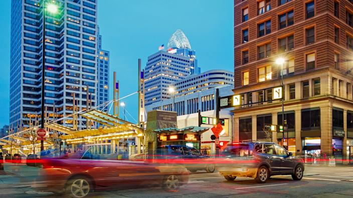 Glimpse of city life with traffic on Walnut Street with office buildings in the background in downtown Cincinnati, Ohio, USA illuminated at twilight.