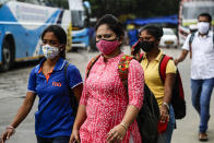 People wearing face masks walk to catch buses in Kolkata, India, Friday, Aug. 14, 2020. India's coronavirus death toll overtook Britain's to become the fourth-highest in the world with another single-day record increase in cases Friday. (AP Photo/Bikas Das)