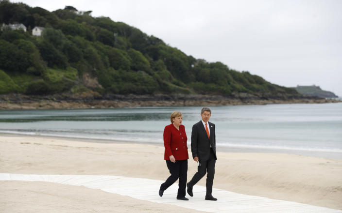 German Chancellor Angela Merkel and her spouse Joachim Sauer arrive for the G7 meeting at the Carbis Bay Hotel in Carbis Bay, St. Ives, Cornwall, England, Friday, June 11, 2021. Leaders of the G7 begin their first of three days of meetings on Friday, in which they will discuss COVID-19, climate, foreign policy and the economy. (Phil Noble, Pool via AP)