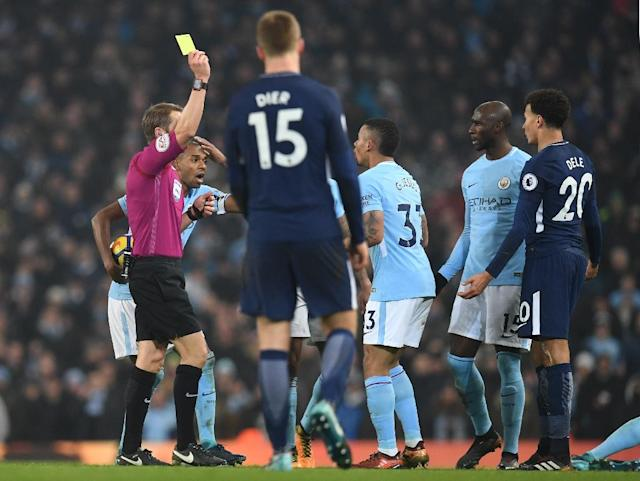 Tottenham Hotspur's Dele Alli (R) receives a yellow card for an ugly ankle-high challenge on Manchester City's Kevin De Bruyne (AFP Photo/Paul ELLIS)