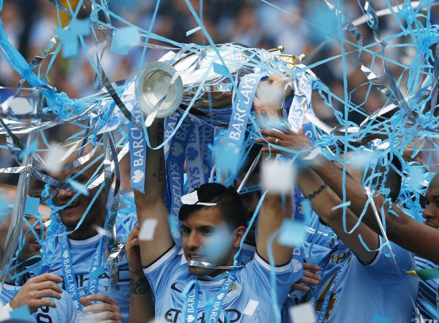 """Manchester City's Sergio Aguero celebrates with the English Premier League trophy following their soccer match against West Ham United at the Etihad Stadium in Manchester, northern England May 11, 2014. REUTERS/Darren Staples (BRITAIN - Tags: SPORT SOCCER) FOR EDITORIAL USE ONLY. NOT FOR SALE FOR MARKETING OR ADVERTISING CAMPAIGNS. NO USE WITH UNAUTHORIZED AUDIO, VIDEO, DATA, FIXTURE LISTS, CLUB/LEAGUE LOGOS OR """"LIVE"""" SERVICES. ONLINE IN-MATCH USE LIMITED TO 45 IMAGES, NO VIDEO EMULATION. NO USE IN BETTING, GAMES OR SINGLE CLUB/LEAGUE/PLAYER PUBLICATIONS"""