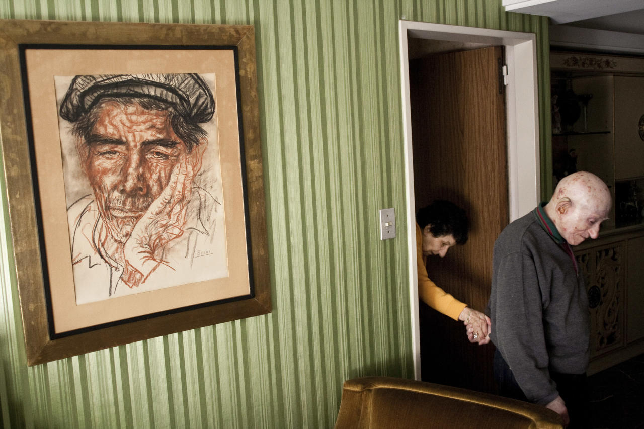 "In this photo provided on Friday Feb. 10, 2012 by World Press Photo, the 1st prize Daily Life Stories of the 2012 World Press Photo contest by Alejandro Kirchuk, Argentina ""Never Let You Go"". Marcos leads Monica from their room to the living room in Buenos Aires. Monica was diagnosed with Alzheimer's disease. (AP Photo/Alejandro Kirchuk)"