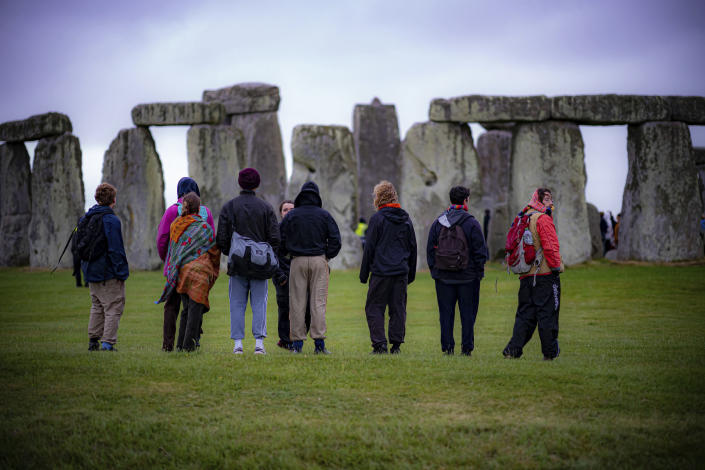 People view the stones during Summer Solstice at Stonehenge, where some people jumped over the fence to enter the stone-circle to watch the sun rise at dawn of the longest day of the year in the UK, in Amesbury, England, Monday June 21, 2021. The prehistoric monument of ancient stones have been officially closed for the celebrations due to the coronavirus lockdown, but groups of people ignored the lockdown to mark the Solstice, watched by low key security. (Ben Birchall/PA via AP)