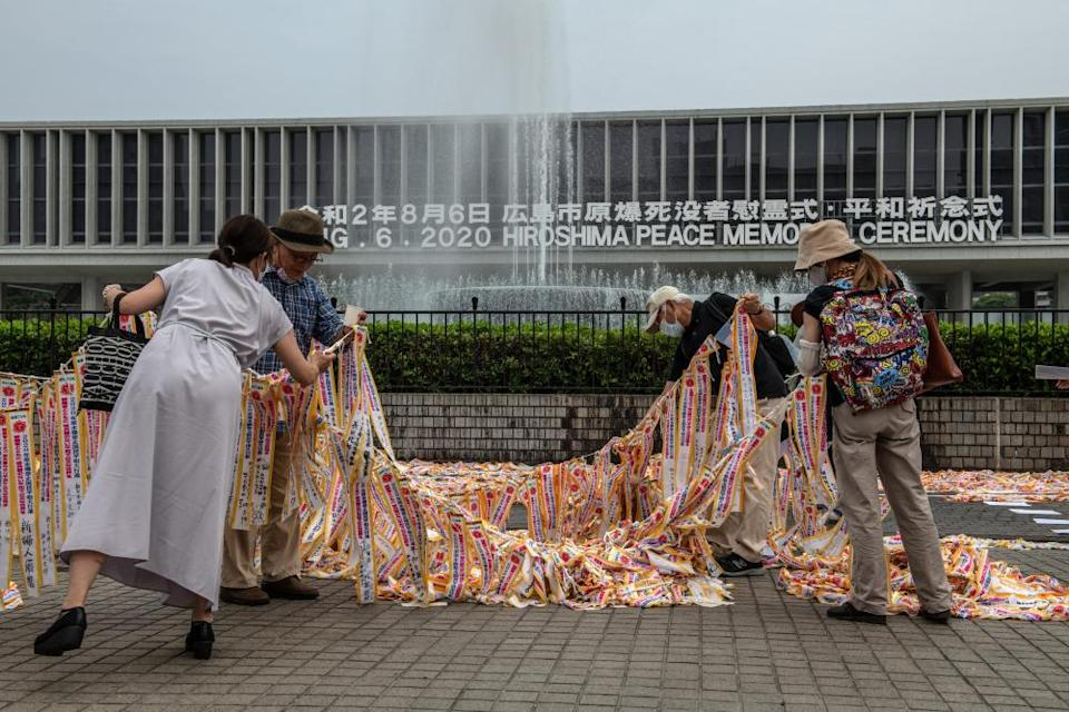 """<span class=""""element-image__caption"""">Peace activists arrange ribbons near the Hiroshima memorial museum. About 140,000 people were killed in the bombing.</span> <span class=""""element-image__credit"""">Photograph: Carl Court/Getty Images</span>"""