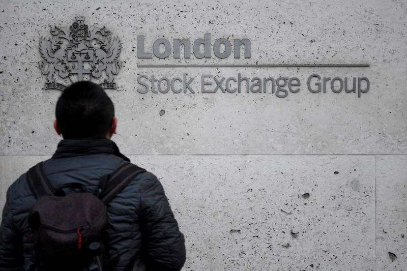 FILE PHOTO: People walk past the London Stock Exchange Group offices in the City of London, Britain