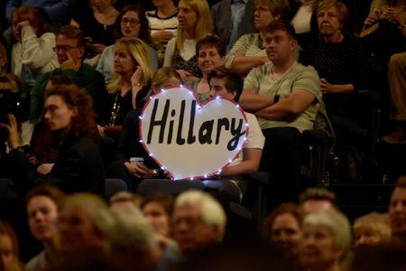 Members of the audience hold a sign as former U.S. Secretary of State, Hillary Clinton is interviewed by Mariella Frostrup at the Cheltenham Literature Festival in Cheltenham, Britain October 15, 2017. REUTERS/Rebecca Naden