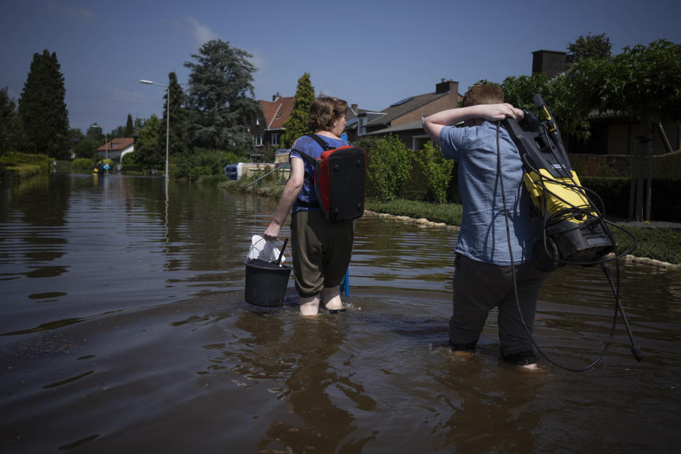 Residents return to their homes with cleaning materials in the town of Brommelen, Netherlands, Saturday, July 17, 2021. In the southern Dutch province of Limburg, which also has been hit hard by flooding, troops piled sandbags to strengthen a 1.1-kilometer (0.7 mile) stretch of dike along the Maas River, and police helped evacuate low-lying neighborhoods. (AP Photo/Bram Janssen)