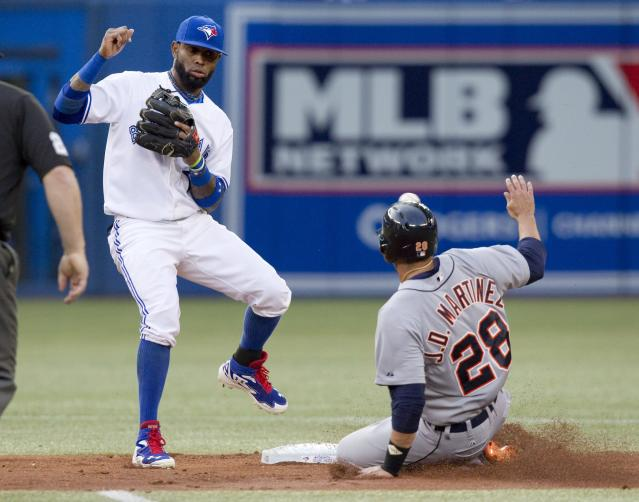 Detroit Tigers' Victor Martinez is safe stealing second base as the ball sails by Toronto Blue Jays shortstop Jose Reyes into center field during the second inning of a baseball game, Friday, Aug. 8, 2014 in Toronto. (AP Photo/The Canadian Press, Fred Thornhill)