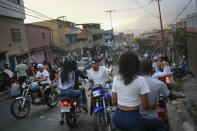 Motorcycle riders gather to see stuntman Pedro Aldana do an exhibition performance in Caracas, Venezuela, Sunday, Jan. 31, 2021. The 33-year-old makes a living with his shows inspiring his young fans who flock to his shop, where he teaches them to change the oil and tune up their bicycles. (AP Photo/Matias Delacroix)