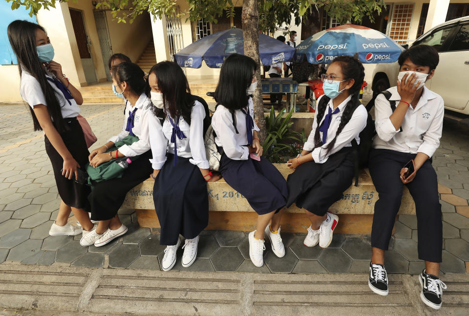 Students wearing face-masks, wait for their morning school class at Santhormok high school, in Phnom Penh, Cambodia, Monday, Nov. 2, 2020. Schools throughout Cambodia reopened Monday for the first time since March but with class sizes and hours limited by coronavirus precautions. (AP Photo/Heng Sinith)