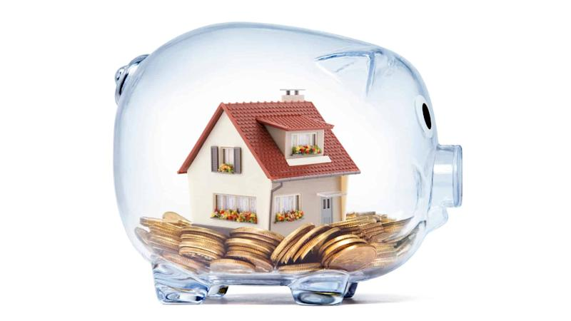 Transparent piggy bank with house deposit