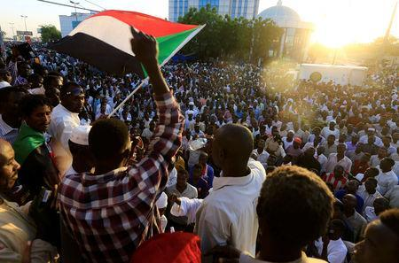 Sudanese demonstrators wave their national flags as they attend a mass anti-government protest outside Defence Ministry in Khartoum, Sudan April 21, 2019. REUTERS/Mohamed Nureldin Abdallah