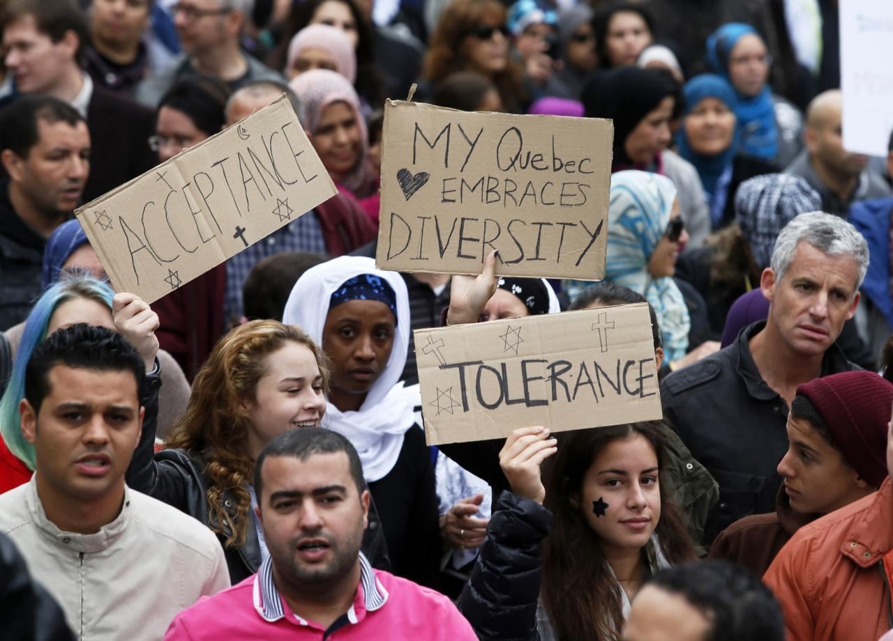 Demonstrators hold signs as they protest against Quebec's proposed Charter of Values in Montreal, September 14, 2013. Thousands took to the streets to denounce the province's proposed bill to ban the wearing of any overt religious garb by government paid employees. REUTERS/ Christinne Muschi (CANADA - Tags: POLITICS CIVIL UNREST RELIGION)