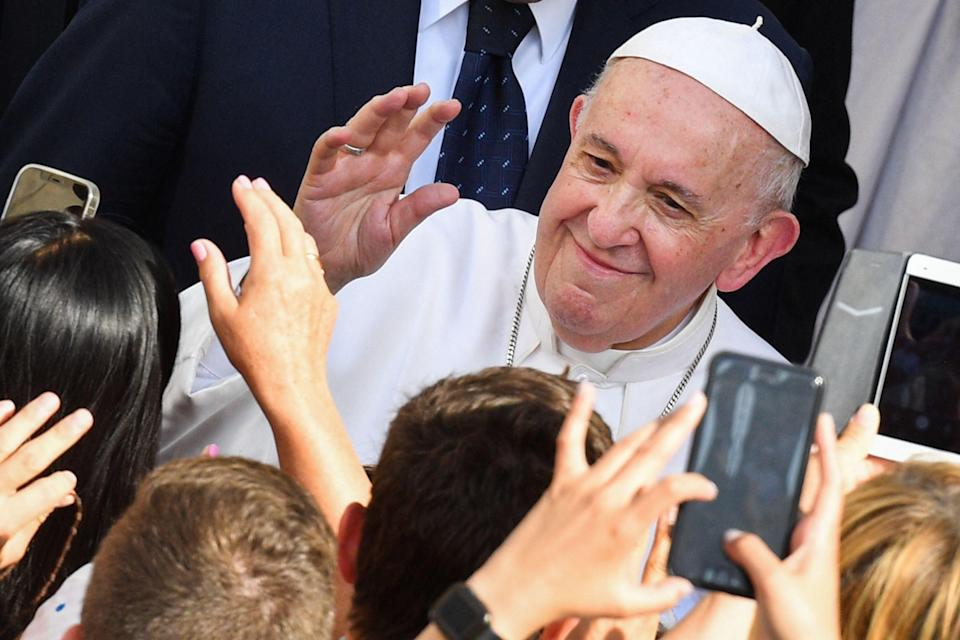 Attendees greet Pope Francis as he arrives to hold his weekly general audience at San Damaso courtyard in The Vatican (AFP via Getty Images)