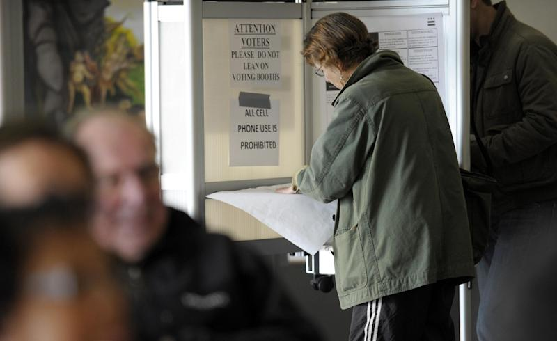 District of Columbia residents, front, wait to cast their vote, as another, behind, participates in early voting in Washington, Wednesday, Oct. 31, 2012. (AP Photo/Susan Walsh)