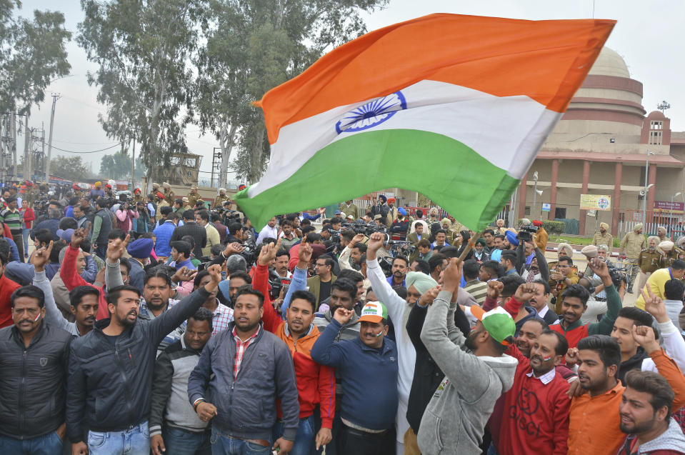 An Indian waves national flag as others shout slogans while they wait to welcome Indian pilot at India Pakistan border at Wagah, 28 kilometers (17.5 miles) from Amritsar, India, Friday, March 1, 2019. Pakistan is preparing to hand over a captured Indian pilot as shelling continued for a third night across the disputed Kashmir border even as the two nuclear-armed neighbors seek to defuse the most serious confrontation in two decades. (AP Photo/Prabhjot Gill)