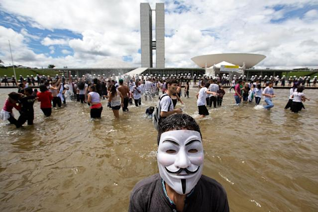 A student wearing a Guy Fawkes mask takes part in a protest in front of the National Congress, in Brasilia, Brazil, Wednesday, March 26, 2014. The protest was organized by the National Union of Students to press deputies to approve the National Education Plan and allocate of 10% of the gross domestic product for education. (AP Photo/Eraldo Peres)