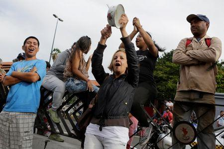 A woman bangs a pot during a protest over food shortage and against Venezuela's government in Caracas