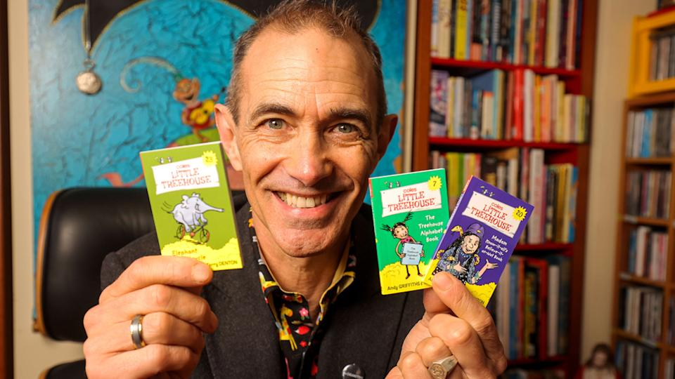 Pictured is author Andy Griffiths holding some of the  Little Treehouse books.