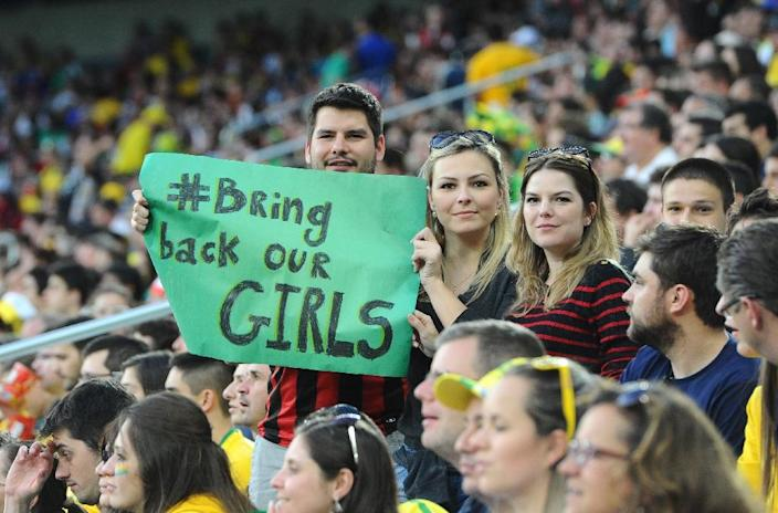 """Football fans at the 2014 World Cup, during a match between Iran and Nigeria, display signs supporting the """"Bring back our girls"""" campaign (AFP Photo/Jewel Samad)"""