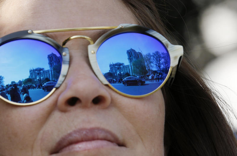 The Notre Dame Cathedral is reflected in the sunglasses of an onlooker in Paris, Thursday, April 18, 2019. Nearly $1 billion has already poured in from ordinary worshippers and high-powered magnates around the world to restore Notre Dame Cathedral in Paris after a massive fire. (AP Photo/Christophe Ena)