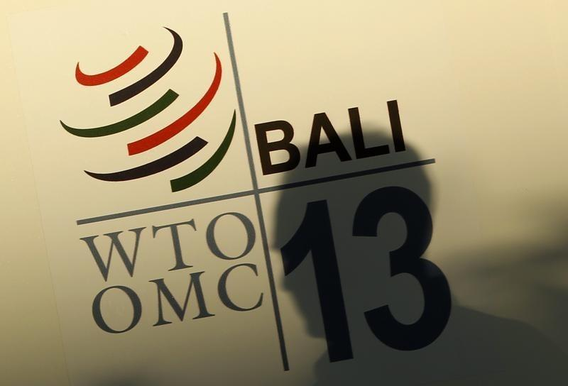 Man walks past a WTO logo in Nusa Dua