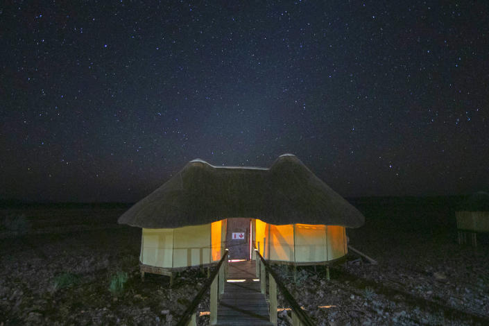 Glowing lights from a bush chalet at Sossusvlei desert camp, as the Namibian skies fill with stars. (Photo: Gordon Donovan/Yahoo News)