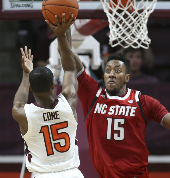 Virginia Tech's Jalen Cone (15) has his shot blocked by North Carolina State's Manny Bates (15) in the first half of an NCAA college basketball game Saturday, Jan. 11, 2020, in Blacksburg, Va. (Matt Gentry/The Roanoke Times via AP)