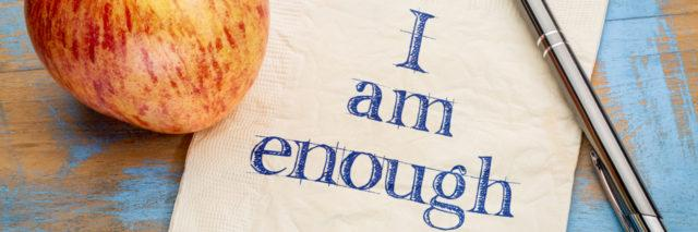 I am enough positive affirmation - handwriting on a paper with a fresh apple nearby.